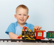 Little boy playing with a toy locomotive Stock Photography