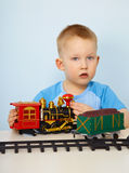 Little boy playing with a toy locomotive Stock Photos