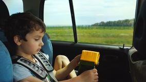 Little Boy Playing With The Toy In The Moving Car stock video