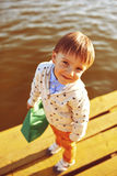 Little boy playing with toy paper ship by the lake Stock Images