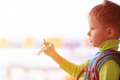 Little boy playing with toy plane in the airport Royalty Free Stock Image