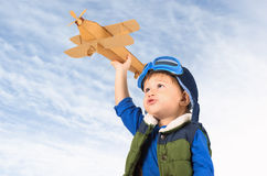Little boy playing with toy plane. Little boy playing with handmade cardboard toy plane against blue sky Royalty Free Stock Photography