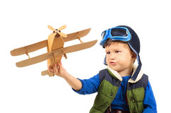 Little boy playing with toy plane. Little boy playing with handmade cardboard toy plane isolated on white background Stock Image