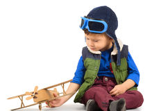 Little boy playing with toy plane. Little boy playing with handmade cardboard toy plane sitting on the floor isolated on white background Stock Images