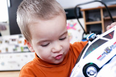 Little boy playing with toy police car. Cute child playing in the room with police car Stock Photos