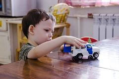 a little boy is playing with a toy police car royalty free stock image