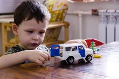 a little boy is playing with a toy police car royalty free stock images