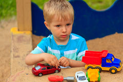Little boy playing with toy trucks Stock Photo