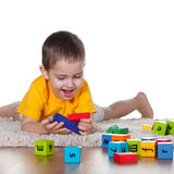 Little boy playing toys on the carpet Stock Image
