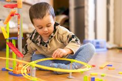 The little boy is playing toys in the room. sunny day. stock photography