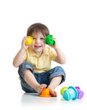 Little boy playing with toys while sitting on Stock Images