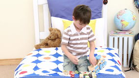 Little boy playing with a train in his bedroom stock video