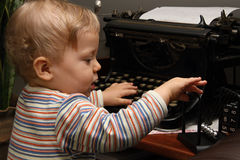 Little boy playing with typewriter and Newtons cradle Stock Image