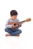 Little boy playing the ukulele stock photo