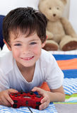 Little boy playing video games. And lying on bed Stock Photography