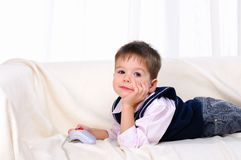 Little boy playing video games. Lying on the couch Royalty Free Stock Photography