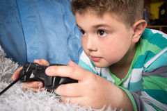Little boy playing video games Stock Images