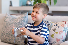 Little boy playing video games on the couch. At home in the living room Royalty Free Stock Photography
