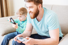 Little boy playing video games with dad sitting on sofa Stock Photos