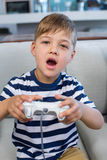 Little boy playing video games. At home in the living room Royalty Free Stock Photo
