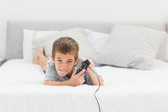 Little boy playing video games lying on bed Royalty Free Stock Image