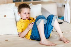 Boy playing video games on portable device. Little boy playing video games on portable console or mobile phone Stock Photography