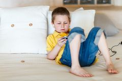 Boy playing video games on portable device. Little boy playing video games on portable console or mobile phone Royalty Free Stock Image