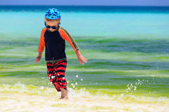 Little boy playing with water on the beach Stock Image