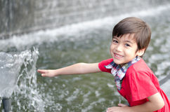 Little boy playing water the fountain Stock Photos