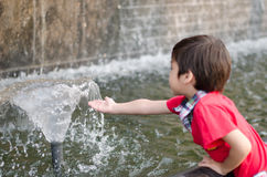 Little boy playing water the fountain Royalty Free Stock Photo