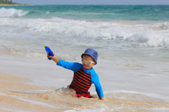 Little boy playing with water gun on the beach Stock Photography