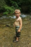 Wet little blond boy playing in the creek waterCherokee Tennesee. Happy smiling little blond boy playing with rocks in the creek in Cherokee North Carolina royalty free stock images