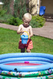Little boy playing with water near the children's pool on the la Royalty Free Stock Photos