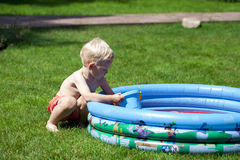 Little boy playing with water near the children's pool on the la Royalty Free Stock Image
