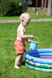 Little boy playing with water near the children's pool on the la Royalty Free Stock Photography