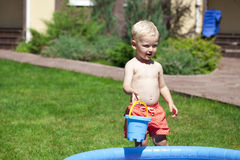 Little boy playing with water near the children's pool on the la Royalty Free Stock Photo