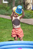 Little boy playing with water near the children's pool on the la Stock Photography