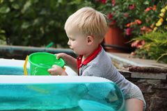 A little boy is playing with water near an inflatable pool. Summer and family holidays. Happy childhood royalty free stock images