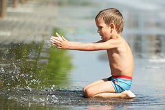Little boy playing with water in a puddle Royalty Free Stock Photos