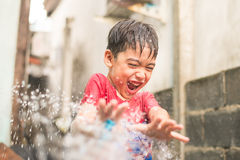 Little boy playing water splash over face Stock Photo
