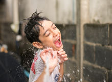 Little boy playing water splash over face Stock Photography