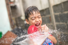 Little boy playing water splash over face Stock Image