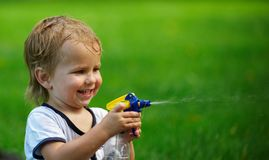 Little boy playing with water spray on hot summer day. Royalty Free Stock Images
