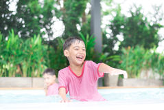 Little boy playing water at swimming pool in the hotel Royalty Free Stock Photo