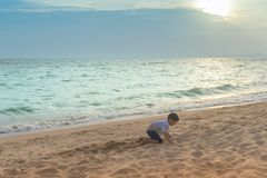 Little boy playing with wave and sand in Pattaya Beach Thailand royalty free stock photography