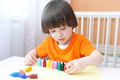 Little boy playing with wax pencils Stock Photography