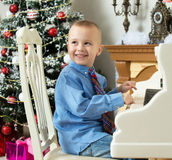 Little boy playing on a white Grand piano. Elegant little boy in shirt and tie playing on a white Grand piano. Around the Christmas tree and the fireplace in royalty free stock images