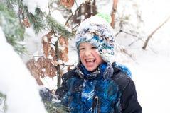 Little boy playing among winter firs Royalty Free Stock Photo