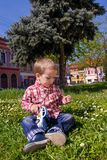 Little Boy Playing With Grass And Toy Police Car In Nature