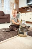 Little boy playing withcooking pots. Little boy sitting on carpet in kitchen playing with cooking pots Stock Image